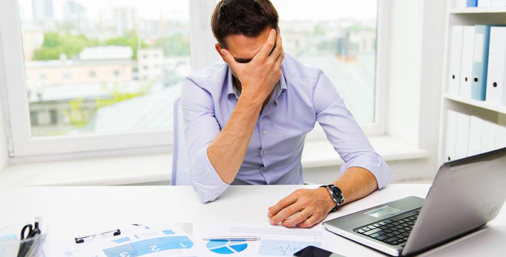 Gjeld bedrift - En bedriftsleder er fortvilet på kontoret sitt